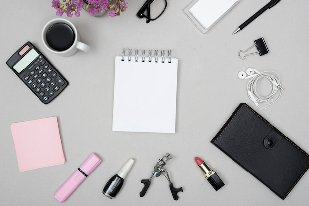 Vista superior de la libreta en blanco rodeada por la taza de café; calculadora; objetos de maquillaje y auriculares sobre fondo gris.