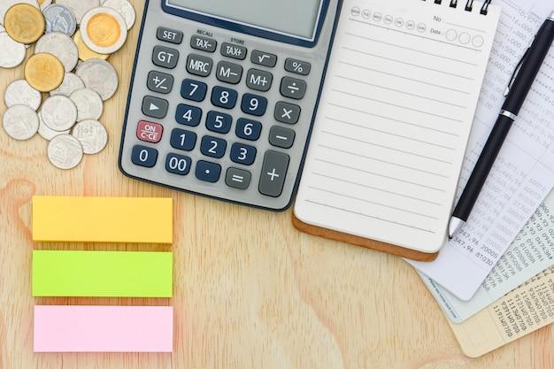 Vista superior de las libretas de ahorro, la calculadora, el cuaderno y la pila de monedas en el fondo de madera