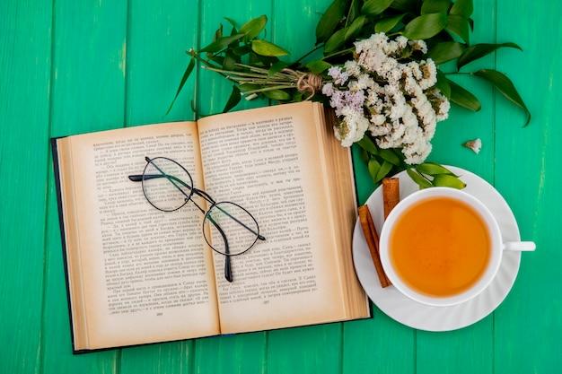 Vista superior del libro abierto con flores de gafas ópticas y una taza de té con canela sobre una superficie verde