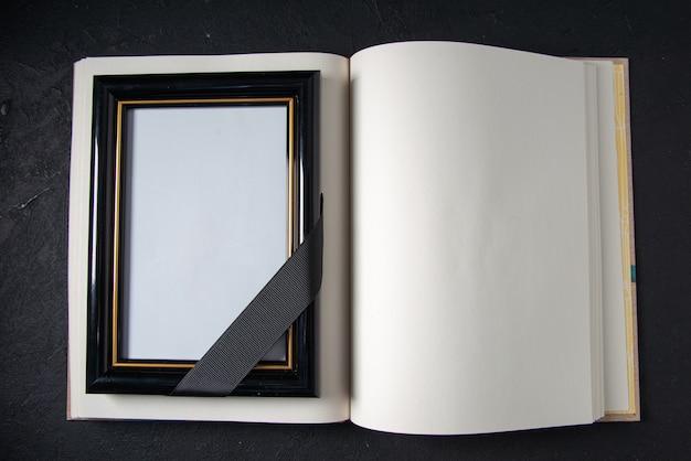 Vista superior del libro abierto con marco de fotos en la pared oscura