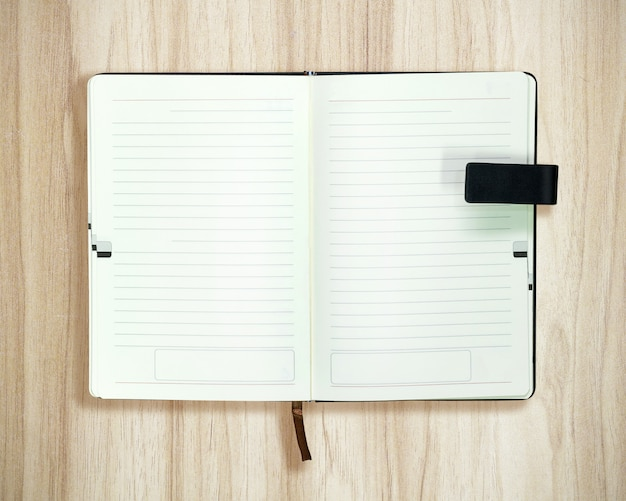 Vista superior del libro abierto sobre fondo de madera. plantilla en blanco de papel blanco.
