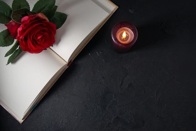 Vista superior del libro abierto con vela y flor roja en la pared oscura