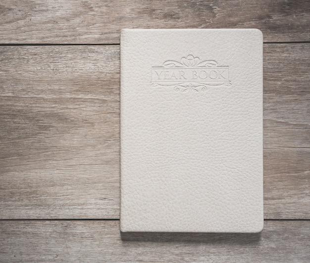 Vista superior del libro blanco sobre fondo de tablón de madera vieja