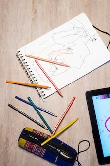 Vista superior del libro de ejercicios abierto, lápices de colores y tableta en el escritorio blanco