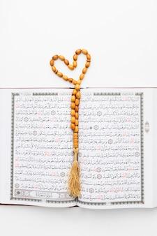 Vista superior del libro islámico del corán con misbaha