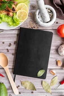 Vista superior del libro de menú con hojas de laurel y ensalada