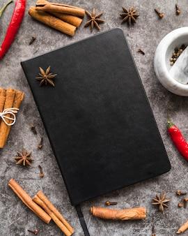 Vista superior del libro de menú con palitos de canela y anís estrellado