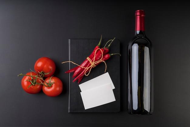 Vista superior del libro de menú vacío con botella de vino y tomates