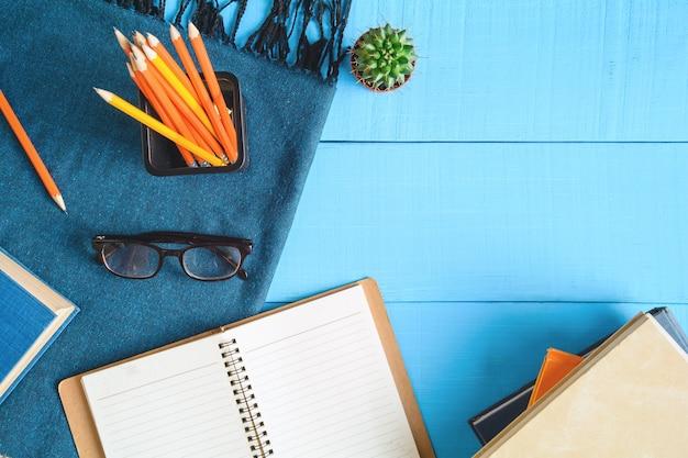 Vista superior libro y nota de lápiz en la mesa de madera azul