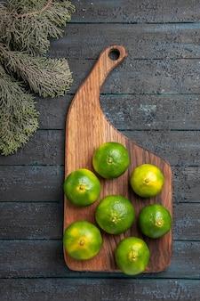 Vista superior de limas y ramas lejanas limas en el tablero de la cocina junto a las ramas de los árboles