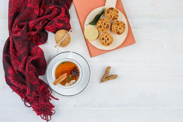 Vista superior de limón, galletas con chispas de chocolate en un plato con pañuelo rojo, galletas blancas, canela y un libro sobre la superficie blanca