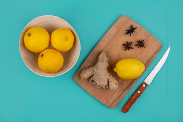Vista superior de limón con jengibre sobre tabla de cortar y cuchillo con tazón de limones sobre fondo azul.
