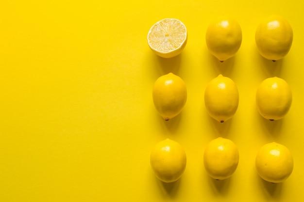 Vista superior de limón maduro entero y en rodajas en varias filas sobre una superficie amarilla, concepto de salud y vitaminas