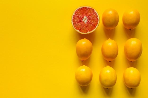 Vista superior de limón y pomelo maduro entero y en rodajas en varias filas sobre una superficie amarilla, concepto de salud y vitaminas