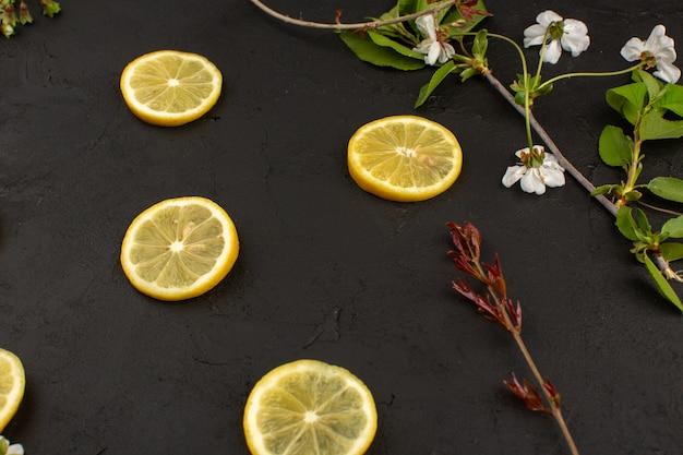 Vista superior limón en rodajas agrio suave jugoso alrededor de flores blancas en la oscuridad