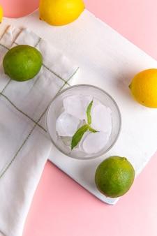 Vista superior de limonada fría fresca con hielo junto con limones frescos en la superficie rosa