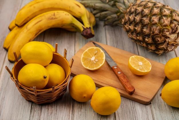 Vista superior de limones en un balde con medio limón sobre una tabla de cocina de madera con un cuchillo con limones, plátanos y piña aislado en una superficie de madera gris