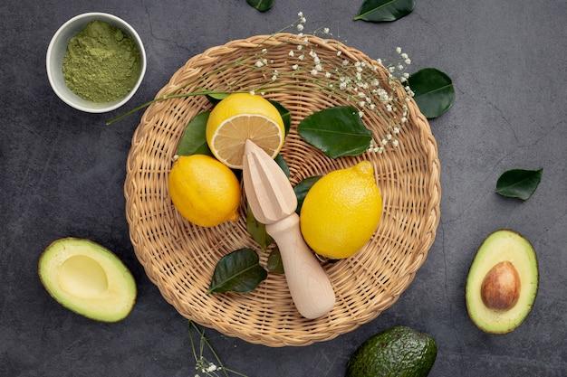 Vista superior de limones en canasta con aguacate