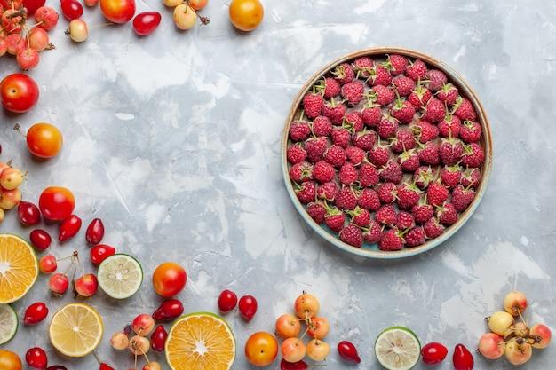 Vista superior de limones y cerezas frutas frescas con frambuesas rojas en la mesa de luz fruta fresca madura suave