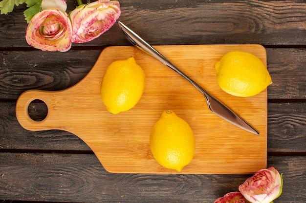 Una vista superior limones frescos agrios maduros cítricos suaves jugosos junto con flores secas vitamina tropical amarilla en el escritorio rústico marrón