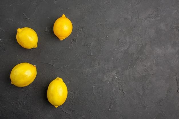 Vista superior de limones frescos forrados en una mesa oscura, fruta amarilla cítrica, espacio libre para texto
