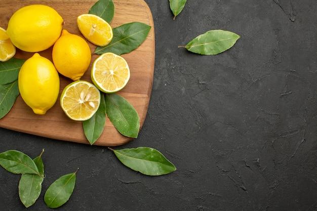 Vista superior de limones frescos frutas ácidas en frutas cítricas de mesa oscura