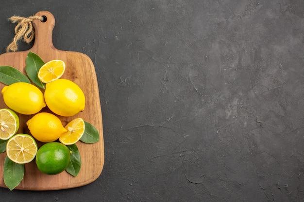 Vista superior de limones frescos frutas ácidas en la mesa de color gris oscuro, cítricos, frutas de limón.