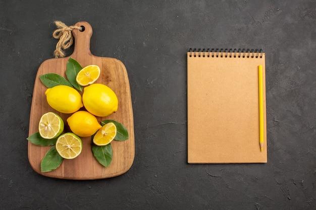 Vista superior limones frescos frutas ácidas en la mesa de color gris oscuro cítricos lima