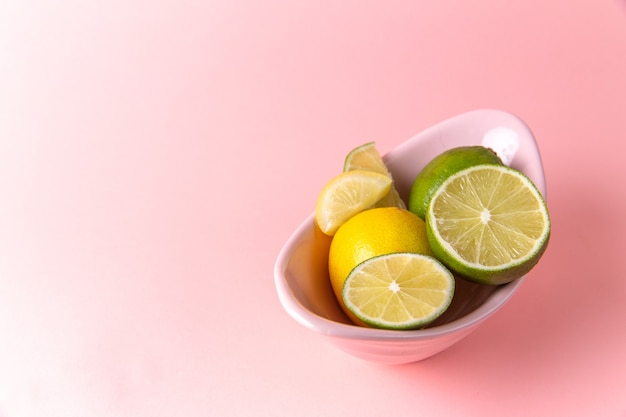 Vista superior de limones frescos con rodajas de limón dentro de la placa sobre la superficie rosa