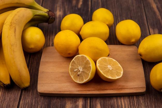 Vista superior de limones frescos en una tabla de cocina de madera con limones y plátanos aislado en una superficie de madera