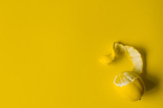 Vista superior de limones maduros enteros y en rodajas sobre una superficie amarilla, concepto de salud y vitaminas