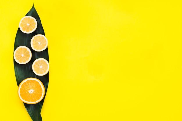 Vista superior de limones y naranja sobre hoja.