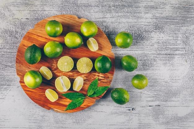Vista superior de limones verdes en plataforma de madera con rodajas y hojas sobre fondo de madera gris. horizontal