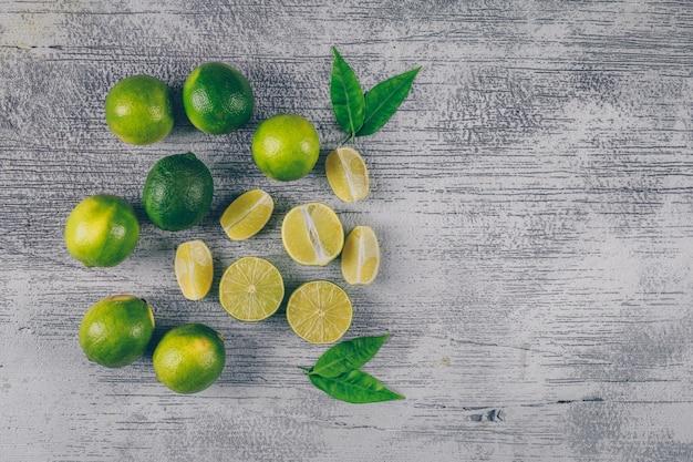 Vista superior de limones verdes con rodajas y hojas sobre fondo de madera gris. espacio horizontal para texto