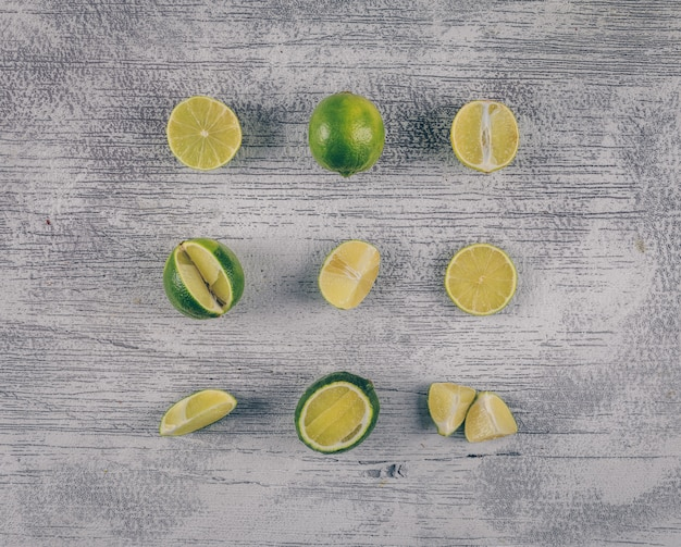 Vista superior de limones verdes con rodajas sobre fondo de madera gris. horizontal