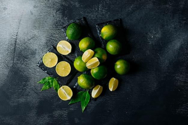 Vista superior de limones verdes con rodajas sobre fondo negro con textura. horizontal