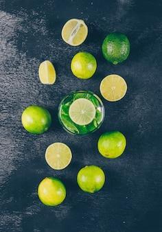 Vista superior de limones verdes en vaso de agua con rodajas sobre fondo negro con textura. vertical