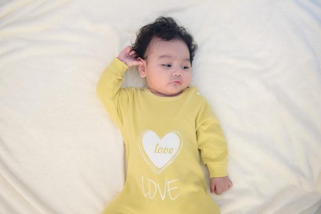 Vista superior de la linda niña asiática acostada en la cama blanca