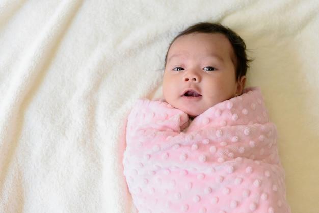 Vista superior de una linda niña asiática envuelta en un paño rosa en la cama