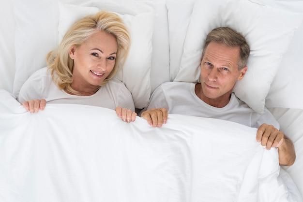 Vista superior linda pareja sentada en la cama
