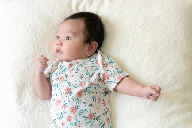 Vista superior del lindo bebé asiático acostado en la cama