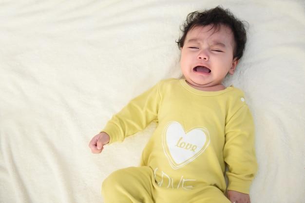 Vista superior de un lindo bebé asiático con un vestido amarillo, acostado en la cama, llorando