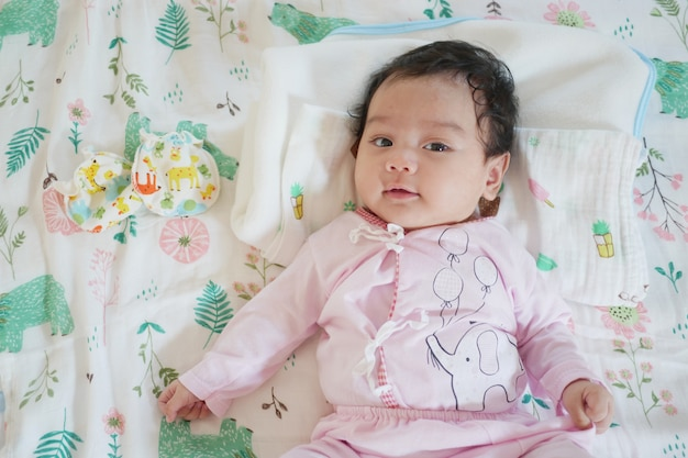 Vista superior de un lindo bebé asiático con un vestido rosa, acostado en la cama, sonriendo y mirando a la cámara