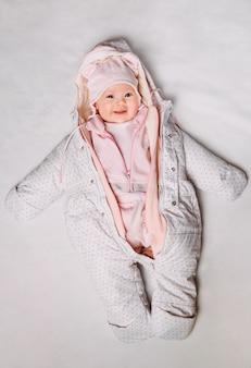 Vista superior de un lindo bebé en una ropa blanca y rosa en la nieve
