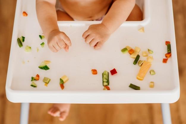 Vista superior lindo bebé en trona comiendo solo