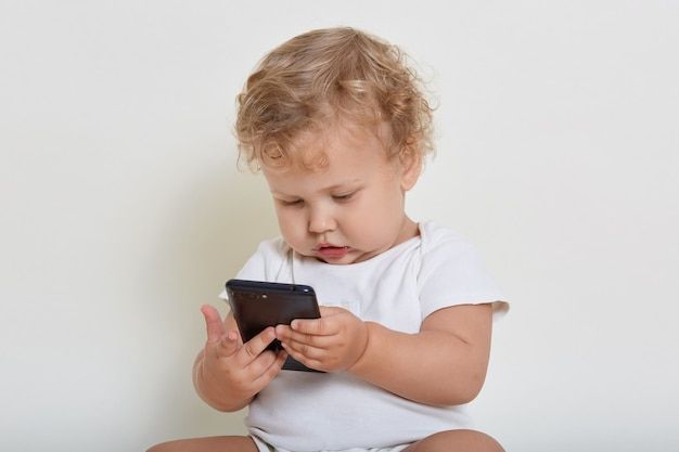 Vista superior del lindo niño rubio sentado en el piso y jugando con teléfonos inteligentes.