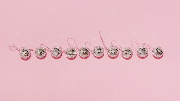 Vista superior de la línea horizontal de bolas de navidad sobre fondo rosa