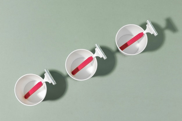 Vista superior de la línea oblicua de vasos de plástico y hojas de afeitar.