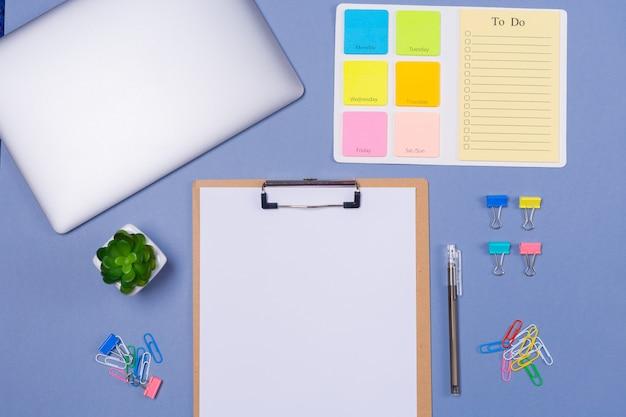 Vista superior de la lista de tareas en blanco para la semana, bolígrafo, papelería y computadora portátil sobre fondo morado claro
