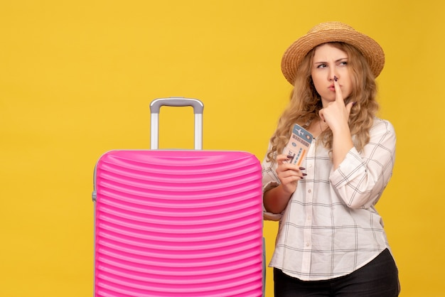 Vista superior de la lluvia de ideas jovencita con sombrero sosteniendo boleto y de pie cerca de su bolso rosa